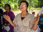 26 DECEMBER 2014 - MAE KHAO, PHUKET, THAILAND:  A Thai Christian woman prays during a memorial service at the Tsunami Memorial Wall in Mae Khao, Phuket. The wall is located at the site that was used as the main morgue for people killed in the tsunami and hosts an annual memorial service. Nearly 5400 people died on Thailand's Andaman during the 2004 Indian Ocean Tsunami that was spawned by an undersea earthquake off the Indonesian coast on Dec 26, 2004. In Thailand, many of the dead were tourists from Europe. More than 250,000 people were killed throughout the region, from Thailand to Kenya. There are memorial services across the Thai Andaman coast this weekend.   PHOTO BY JACK KURTZ