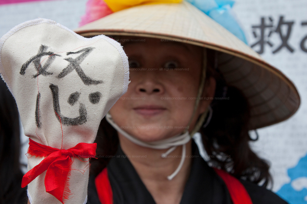 Kiyoko Yamamoto from Hyogo holds  a glove saying anger in the Women's  Protest outside METI (Ministry of Economy, Trade and Industry) in Tokyo, Japan. Friday June 29th 2012. About 400 protesters campaigned the restarting of the Oi nuclear power-station and the policy of Prime-Minister Noda to restart Japan's nuclear power generation programme which has been stalled since the earthquake and tsunami of March 11th 2011 caused meltdown and radiation leaks at the Fukushima Daichi Nuclear power-plant.