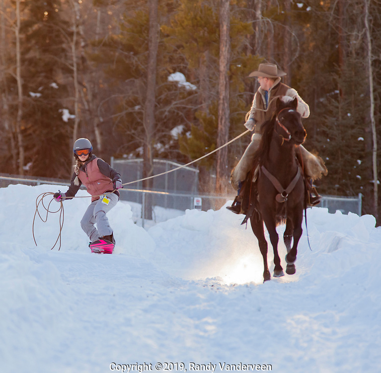 Photo Randy Vanderveen<br /> 2019-03-08<br /> Grande Prairie, Alberta<br /> Paisley, ridden by Ryon Hemingson pulls Margaret Besuijen at the  Thunder in the Pines at Evergreen Park Friday evening. The inaugural skijoring event, which saw someone on skis or a snowboard pulled around by a horse or horse and rider on a closed course proved a popular event at the Foster's Peace Country Ag Classic for both spectators and participants.
