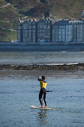© Licensed to London News Pictures. 19/04/2014. Aberystwyth, UK. Two men on paddle boards enjoy the warm sunny weather at the start of Easter Saturday 2014, paddling on the flat calm sea of Cardigan Bay off the beach at Aberystwyth on the west wales coast.. Photo credit : Keith Morris/LNP
