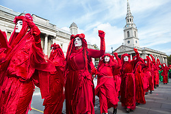 London, UK. 9 October, 2019. Climate activists from the Extinction Rebellion Red Brigade gather in Trafalgar Square on the third day of International Rebellion protests to demand a government declaration of a climate and ecological emergency, a commitment to halting biodiversity loss and net zero carbon emissions by 2025 and for the government to create and be led by the decisions of a Citizens' Assembly on climate and ecological justice.