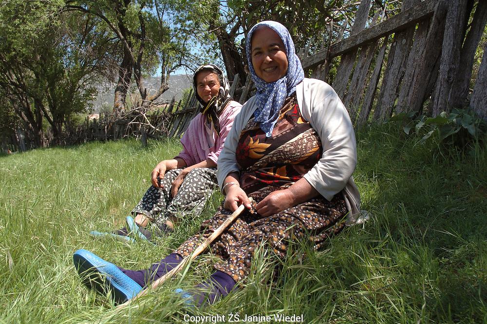 Two Turkish women sitting in a field in Bezirgan a small village in Southern Turkey.