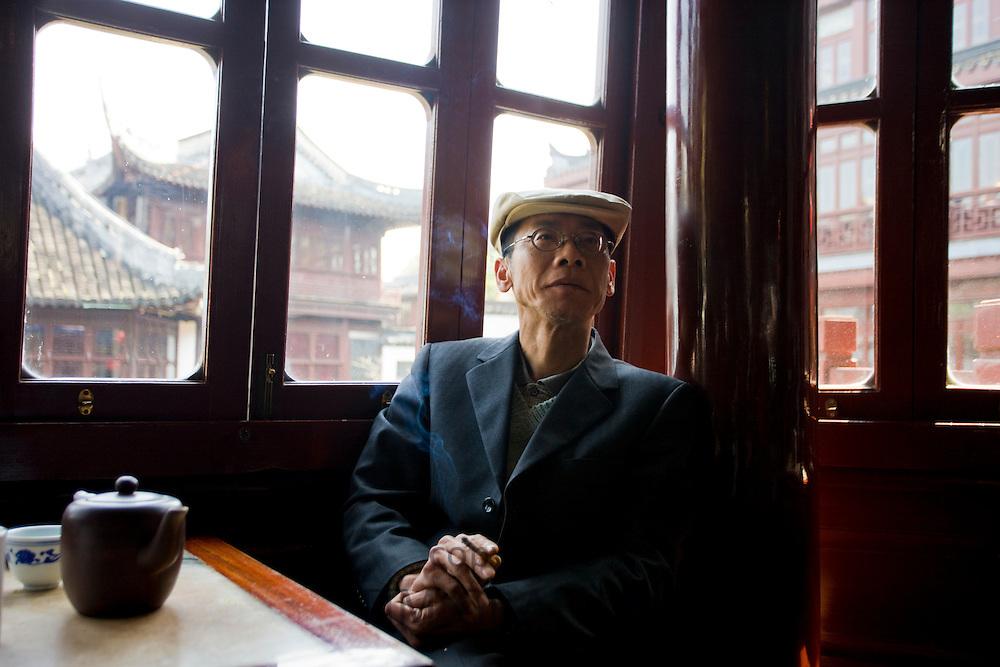 Man drinking tea in the Huxinting Teahouse, Yu Garden Bazaar Market, Shanghai, China