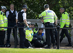 © Licensed to London News Pictures. 24/05/2017. London, UK. Police detain a man opposite Buckingham Palace just before the Changing of the Guard ceremony was due to take place. Today's ceremony has been cancelled.  The terrorism threat level has been raised to critical and Operation Temperer has been deployed. 5,000 troops are taking over patrol duties under police command. Photo credit: Peter Macdiarmid/LNP