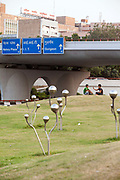 Men sit, relax and use mobile telephones on the greens of traffic roundabouts by the AIIMS Flyover. They sit adjacent to a modern art installation called Sprouts by artist Vibhor Sogani. New Delhi, India