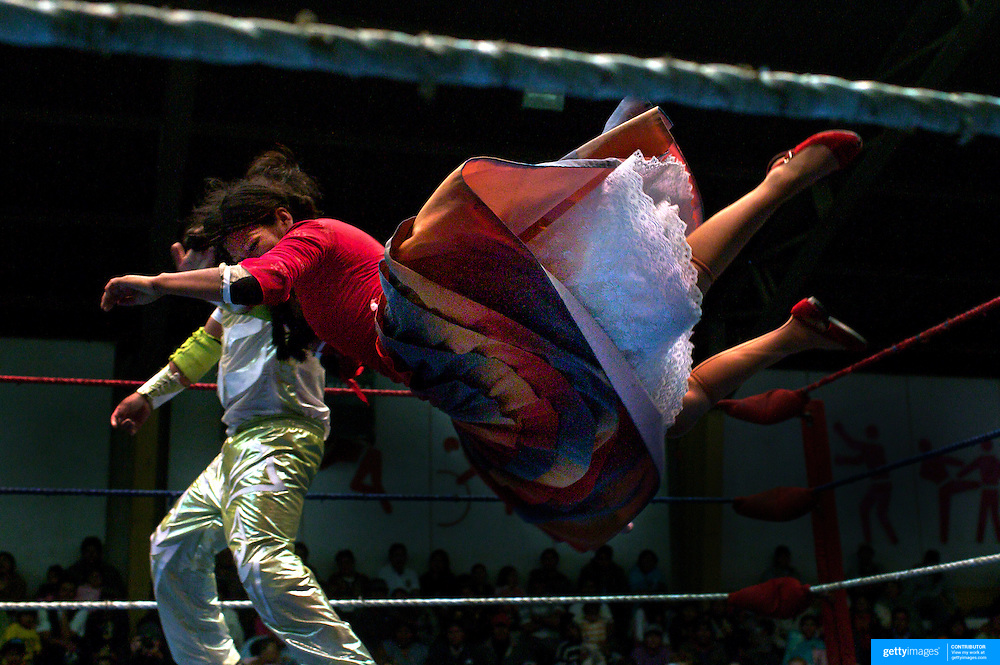 Yolanda la Amorosa dives onto her male counterpart during the 'Titans of the Ring' wrestling group's Sunday performance at El Alto's Multifunctional Centre. Bolivia. The wrestling group includes the fighting Cholitas, a group of Indigenous Female Lucha Libra wrestlers who fight the men as well as each other for just a few dollars appearance money. El Alto, Bolivia, 14th March 2010. Photo Tim Clayton