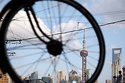 A man rides a bicycle on a street with the skyscrapers of Pudong in the background in Shanghai,  China on 19 October 2010. Shanghai, China's largest city, is quickly becoming one of the major financial centers of the world.