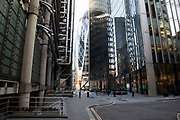 Rush hour beside the Lloyds Building looking towards the Gerkhin in the City of London financial district is virtually deserted due to the Coronavirus outbreak on 23rd March 2020 in London, England, United Kingdom. Following government advice city workers are staying at home to work leaving the streets quiet, empty and eerie. Coronavirus or Covid-19 is a new respiratory illness that has not previously been seen in humans. While much or Europe has been placed into lockdown, the UK government has announced more stringent rules as part of their long term strategy, and in particular social distancing.