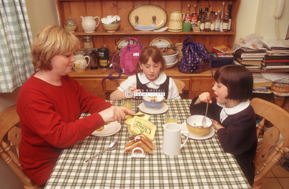 Mother and two young daughters eating breakfast at kitchen table,