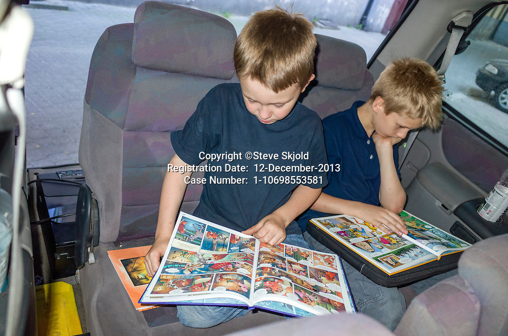Polish boys age 10 and 8 totally adsorbed reading newly acquired comic books in back of family van. Lodz Central Poland