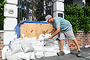 Charleston, South Carolina, USA. 03 September 2019. A workers piles sandbags along a garden entrance of a historic home along the Battery in preparation for Hurricane Dorian September 3, 2019 in Charleston, South Carolina. The slow moving monster storm devastated the Bahamas and is expected to reach Charleston as a Category 2 by Thursday morning.