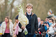 A young member of the public lays flowers In memory of Prince Philip The Royal Highness the Duke of Edinburgh, London on 9 April 2021.