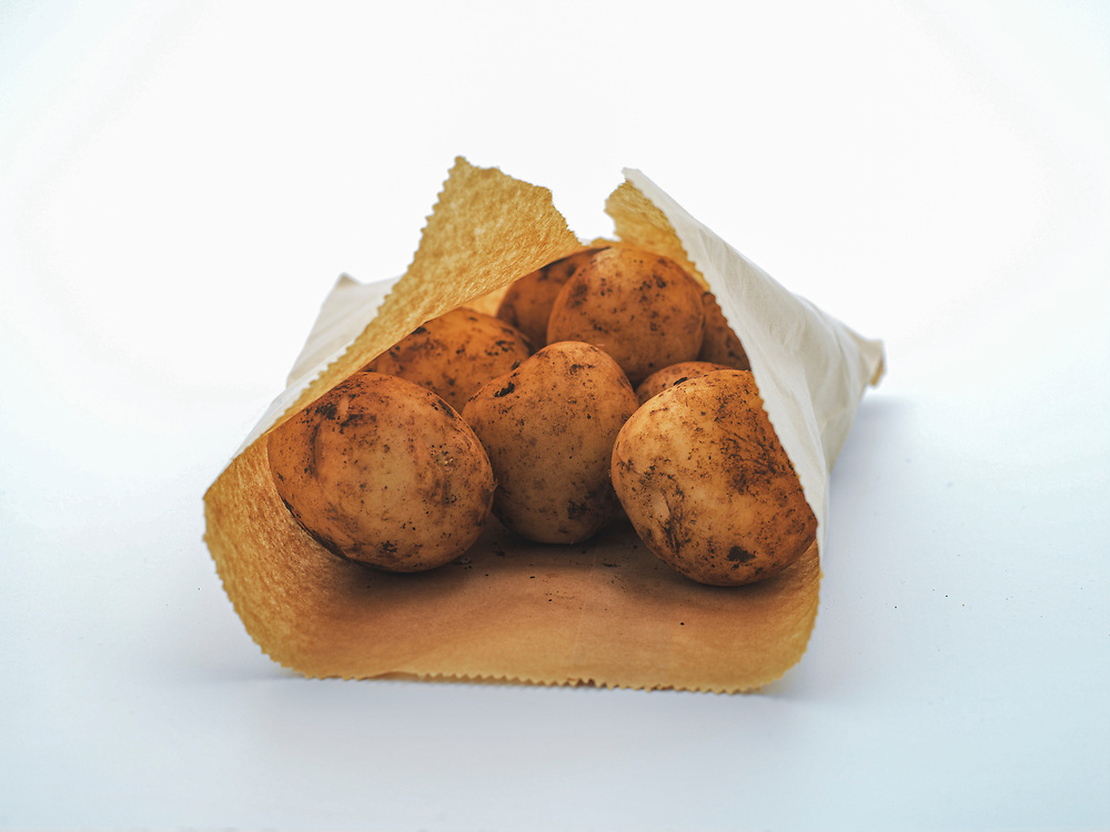 Dirt covered loose Agria potatoes in a brown paper bag.