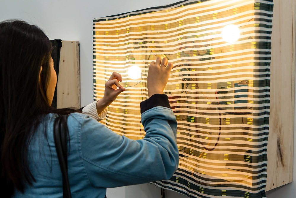 New York, NY - 5 May 2017. The opening day of the Frieze Art Fair, showcasing modern and contemporary art presented by galleries from around the world, on Randall's Island in New York City. A woman works an interactive mixed-media installation by Sergei Tcherepnin at Foksal Gallery.