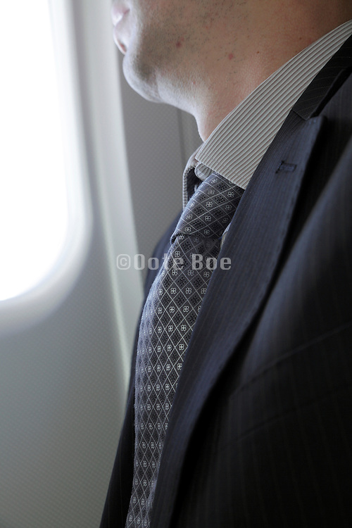 businessman looking out the window of an airplane during flight