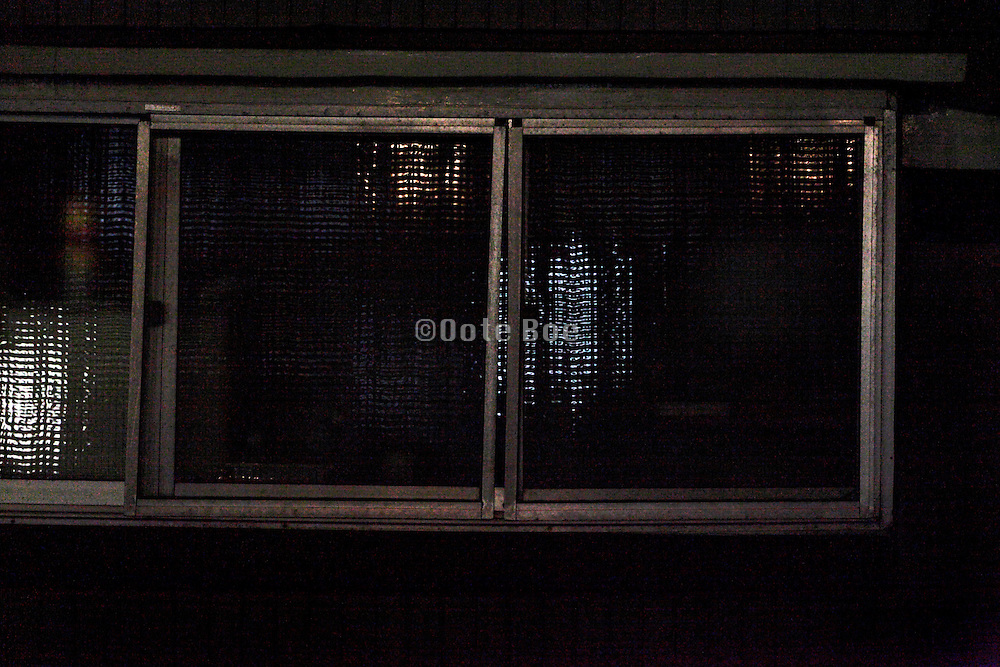 close up of an old small window of a residential house at night