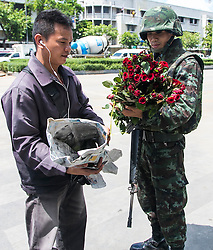 © Licensed to London News Pictures. 23/05/2014. A civilian presents roses to a Thai Army Soldier in Bangkok. Thailand's army said on May 23 that 155 prominent figures, including Yingluck and ousted government leaders, were banned from leaving the country without permission following a military coup.  Photo credit : Asanka Brendon Ratnayake/LNP
