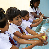 """Grade 4 Childrens Brigade students washing their hands in UNICEF-supplied sinks at the K.M. Vivekanana Vidalayam school in Kalmunai, Ampara Dist. <br /> <br /> The Kalmunai community was tsunami affected and for six months the school grounds became an IDP camp. The school continued teaching during this time in a local temple. The school is known as a """"Child Friendly School"""". Unicef has provided sanitary facilities: boys and girls toilets and hand washing area. Immediately after the tsunami, Unicef supplied books to the school. Unicef has trained teachers in child friendly education and in the establishment of a Children's Brigade. Children's Brigades are a means of promoting hygiene practice in pupils and encouraging them to disseminate messages of hygiene practice and awareness in the wider community.<br /> <br /> Photo: Tom Pietrasik<br /> Ampara District, Sri Lanka<br /> September 29th 2009"""
