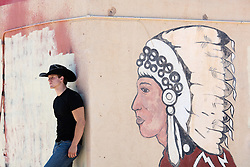 cowboy leaning against a wall with a painted American Indian head