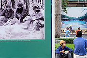 © Licensed to London News Pictures. 07/01/2012. Workmen building a new hotel development have lunch next to a poster featuring a picture from the American war in Siagon, Vietnam. Photo credit : Stephen Simpson/LNP