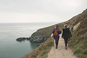 People walk along Howth cliff path overlooking Dublin Bay on 09th April 2017 in County Dublin, Republic of Ireland. Howarth Cliff Path at Howth Head, a peninsula just 15km northeast of Dublin City, is a great day trip for visits to the capital.