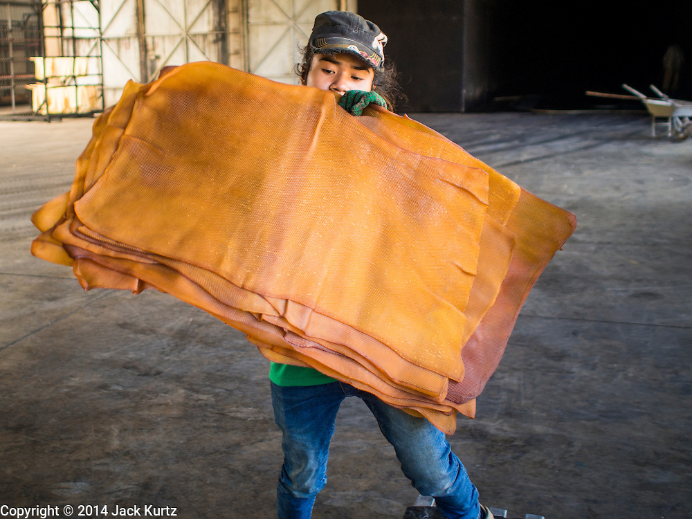 """16 DECEMBER 2014 - CHUM SAENG, RAYONG, THAILAND: A worker hangs rubber sheets to dry before they are put into a smoker at a large rubber plantation near Chum Saeng, Thailand. Thailand is the second leading rubber exporter in the world. In the last two years, the price paid to rubber farmers has plunged from approximately 190 Baht per kilo (about $6.10 US) to 45 Baht per kilo (about $1.20 US). It costs about 65 Baht per kilo to produce rubber ($2.05 US). Prices have plunged 5 percent since September, when rubber was about 52Baht per kilo. Some rubber farmers have taken jobs in the construction trade or in Bangkok to provide for their families during the slump. The Thai government recently announced a """"Rubber Fund"""" to assist small farm owners but said prices won't rebound until production is cut and world demand for rubber picks up.    PHOTO BY JACK KURTZ4 - CHUM SAENG, RAYONG, THAILAND: A worker sorts smoked rubber sheets during the quality control process on a large rubber plantation near Chum Saeng, Thailand. Thailand is the second leading rubber exporter in the world. In the last two years, the price paid to rubber farmers has plunged from approximately 190 Baht per kilo (about $6.10 US) to 45 Baht per kilo (about $1.20 US). It costs about 65 Baht per kilo to produce rubber ($2.05 US). Prices have plunged 5 percent since September, when rubber was about 52Baht per kilo. Some rubber farmers have taken jobs in the construction trade or in Bangkok to provide for their families during the slump. The Thai government recently announced a """"Rubber Fund"""" to assist small farm owners but said prices won't rebound until production is cut and world demand for rubber picks up.    PHOTO BY JACK KURTZ"""