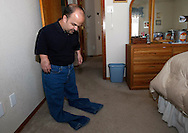 Chris Kotzian tries on a pair of pants at his home in Thornton, Colorado March 25, 2010.  At about four-feet-tall Chris has to have most of his clothes altered. Chris is a achondroplasia dwarf with a rare genetic disorder of bone growth. Preferring to be called a little person Chris is active in the Little People of America, the only dwarfism support organization that includes all 200+ forms of dwarfism.  REUTERS/Rick Wilking (UNITED STATES)