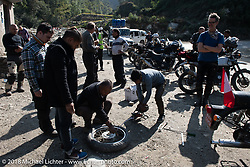 Fixing a flat during a chai stop on day-4 our our Himalayan Heroes adventure riding from Pokhara to Kalopani, Nepal. Friday, November 9, 2018. Photography ©2018 Michael Lichter.