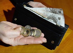 """File photo dated 06/02/17 of a woman holding coins and a purse containing notes. A """"striking"""" surge in consumer complaints about credit, including payday loans, has been seen by the Financial Ombudsman Service (FOS) over the last year."""