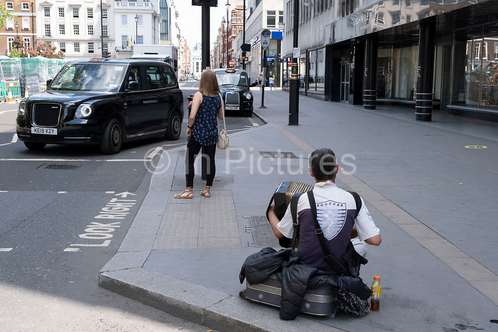 Busker plays the accordian while sitting on the pavement outside John Lewis at Cavendish Square on 26th June 2020 in London, United Kingdom. This street performer is wearing a t-shirt which reads success.