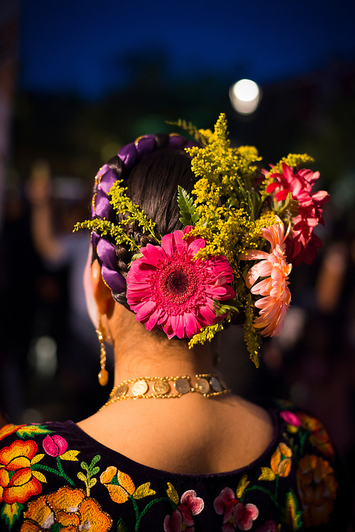 A Mexican woman with flowers in her hair stands outdoors in the city of Oaxaca, Mexico, one of many people celebrating the Day of the Dead (Dia de los Muertos). Her face has also been painted for the festivities as well.