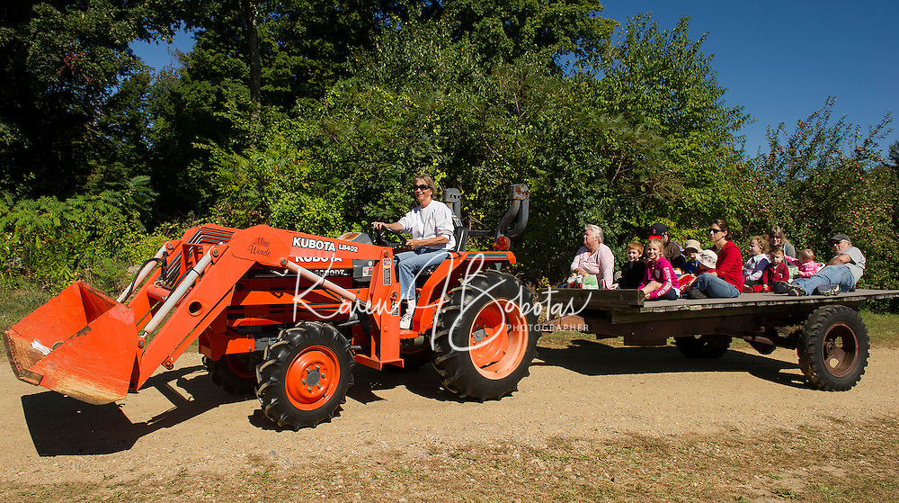 Several families take a ride in on the tractor after apple picking at Smith Orchard in Belmont on Sunday afternoon.  (Karen Bobotas/for the Laconia Daily Sun)