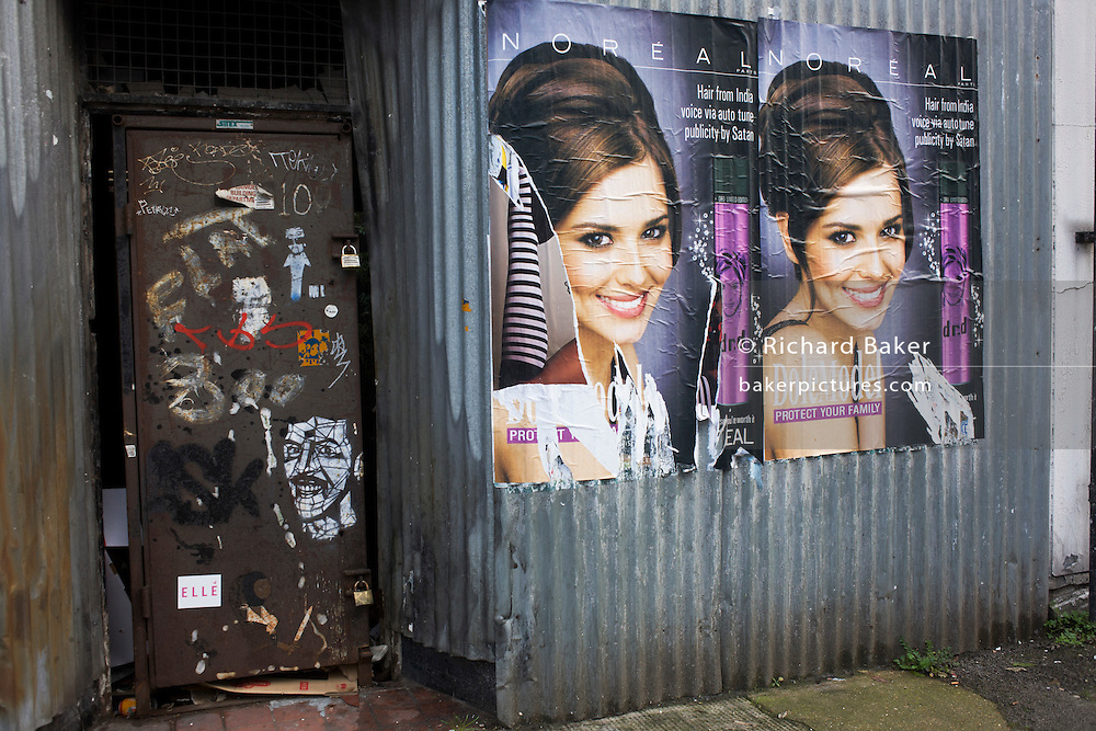 Two Cheryl Cole L'Oreal poster ads next to filthy derelict doorway with stenciled face, a scene of wealth versus poverty.