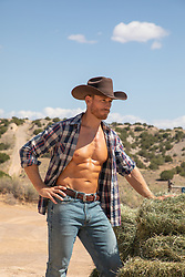 muscular cowboy working on a ranch with hay