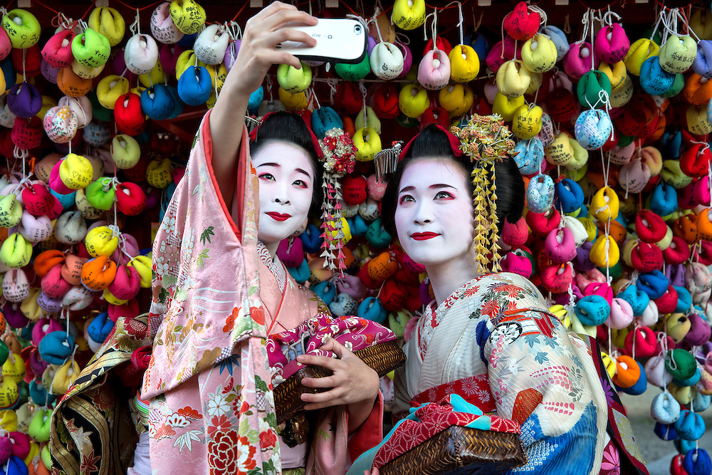 """Two japanese girls take a Selfie in front of the Yasaka Koushindou temple in Kyoto.  The colored pockets are called """"Kukurizaru"""".  It is said that if you dangle a written wish, it will come true."""