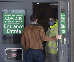 A security guard opens the door for a person entering a COVID-19 assessment facility Saturday, March 14, 2020 in Ottawa, Canada. Photo by THE CANADIAN PRESS/Adrian Wyld/ABACAPRESS.COM