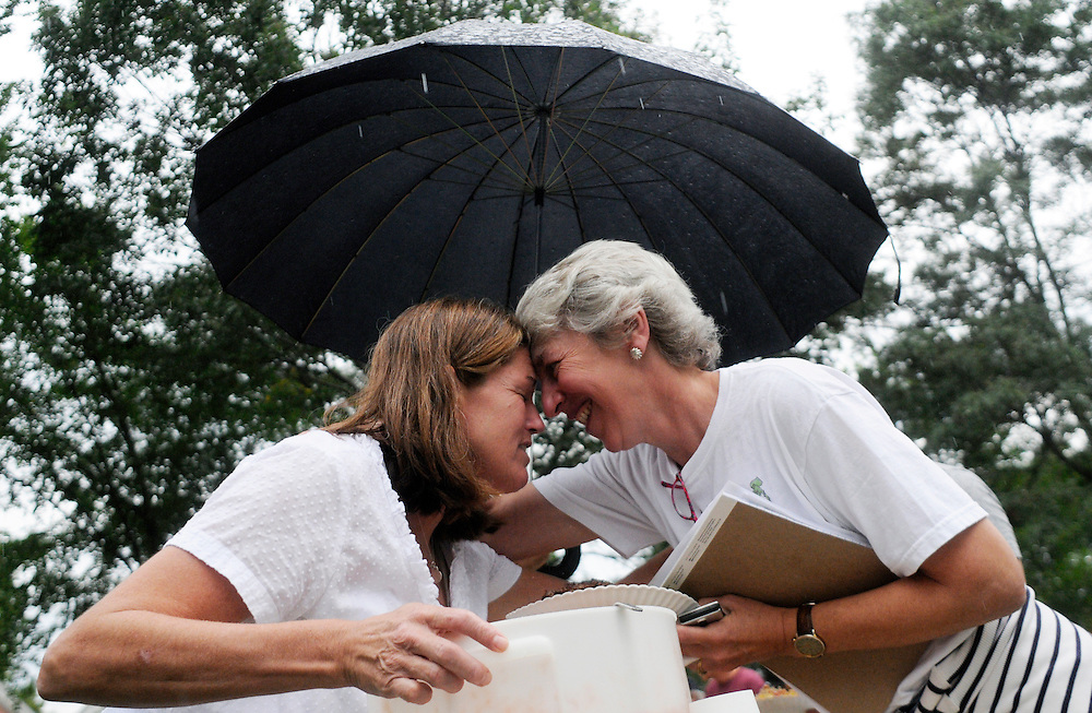 Kate Miller of Woodstock gets a hug after serving Vermont Rep. Alison Clarkson of Woodstock a plate of Gazpacho during a community dinner on the Woodstock green Thursday, September 1, 2011. Volunteers and community members affected by Sunday's flooding were fed at the dinner usually held weekly at the town's Unitarian church. <br /> Valley News - James M. Patterson<br /> jpatterson@vnews.com<br /> photo@vnews.com
