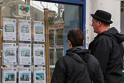 © Licensed to London News Pictures. 29/12/2020. London, UK. A couple view a display of properties for sale in an estate agent's window in north London. According to Halifax, house prices in Islington, north London, have shown the fastest price growth over 2020, with the average property rising 13.4% to £727,922. Neighbouring borough, Hackney, recorded a 1.5% decline to £636,000 to become the second-biggest faller. Photo credit: Dinendra Haria/LNP