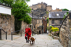 Edinburgh, Scotland, UK. 4 June 2020.  As Covid-19 lockdown relaxation continues in Scotland very few shops and businesses are open. Streets remain quiet and pubs and, with a few exceptions, bars and pubs are closed. Pictured; Elegantly presented Maggie Shapero and her dog Cosmo taking daily exercise on The Miss Jean Brodie Steps in the Old Town. Iain Masterton/Alamy Live News