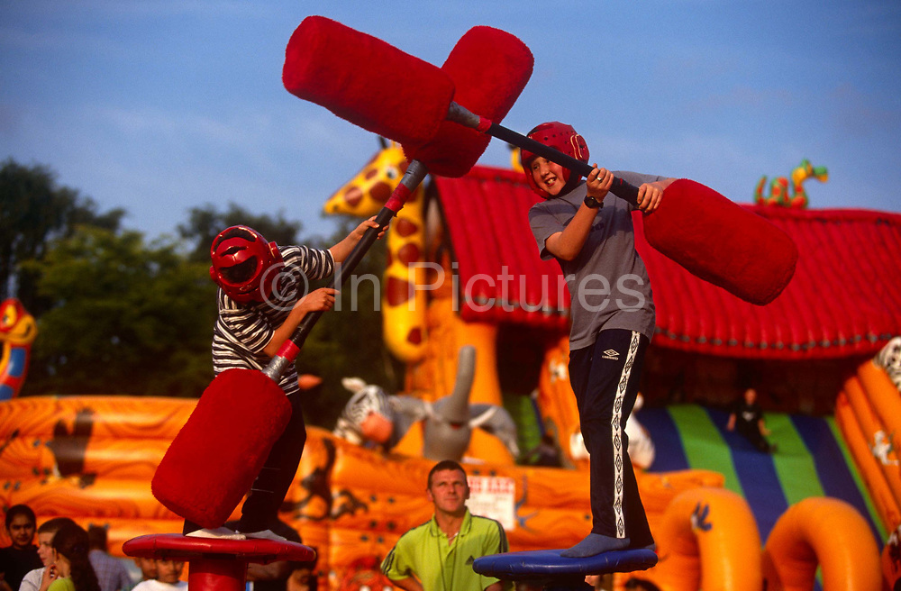 Children battle it out using soft weapons during a Gladiator-style game. Bashing each other on the bodies on high platforms, they use the padded sticks to avoid injury, their heads protected by helmets. An instructor/judge look up to the boys to ensure their safety. In the background is a bouncy castle and other childrens' play area locations.