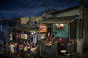 People gather outside a bar in Manaus, Brazil, Sunday, May 24, 2020, amid the new coronavirus pandemic. Although health experts warn that the pandemic is far from over in Manaus, or across the country, national polls show adherence to lockdowns and quarantines falling, and a growing percentage of Brazilians are neglecting local leaders' safety recommendations. (AP Photo/Felipe Dana)