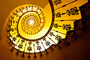 A spiral staircase curves upward in a hotel in Granada, Spain
