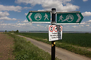 A remote signpost showing the Saxon Shore Way near Halstow on the Kent Thames estuary marshes, potentially threatened by the future London airport. This walking route traverses land that may become part of the development for the new transport hub. With the panoramic views beyond, we see an unspoilt landscape that could controversially become the site for London's estuary airport, built on reclaimed and marshland on the river Thames, east of the city. Current London mayor Boris Johnson is in faviour of this project to alleviate pressure from other airport hubs, regardless of wildlife (especially a nearby protected bird sanctuary).