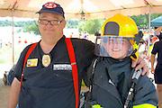 Demonstration of firefighting gear with boy age 11 in jacket and helmet. Aquatennial Beach Bash Minneapolis Minnesota USA