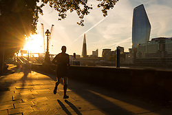 © Licensed to London News Pictures. 24/09/2018. London, UK. A jogger on the Thames path shortly after sunrise on the River Thames during cold but sunny weather this morning.  Photo credit: Vickie Flores/LNP