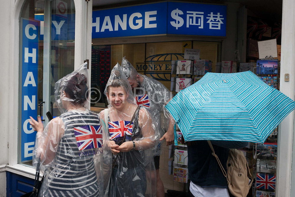 During a downpour, an afternoon of heavy rainfall in London, a group of three tourists wearing matching plastic macs with Union jack flags, emerge from a Bureau de Change in central London on 7th June 2016.