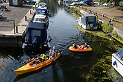 An adult and young children paddle in a canoe and an inflatable through Beccles Quay, on 13th August 2020, in Beccles, Suffolk, England.