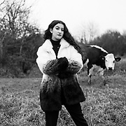 A portrait of Sabine, in Biggleswade, as a Dairy Cow looks on. Credit: Beth Prodger/UoG/Pathos Images