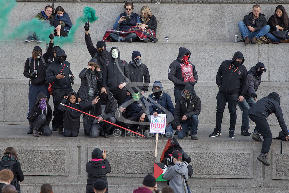 "London, April 16th 2016. Masked Anarchists let off a smoke bomb on the plinth of Nelson's column in Trafalgar Square after thousands of people supported by trade unions and other rights organisations demonstrate against the policies of the Tory government, including austerity and perceived favouring of ""the rich"" over ""the poor""."