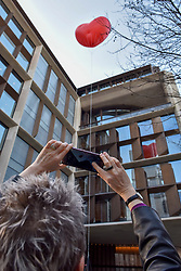 """© Licensed to London News Pictures. 15/02/2018. LONDON, UK.  London, UK.  15 February 2018.  A woman photographs a giant chubby heart balloon outside Bloomberg's HQ in Queen Victoria Street during """"Chubby Hearts Over London"""", a design project conceived by Anya Hindmarch.  Supported by the Mayor of London, the British Fashion Council and the City of Westminster giant chubby heart balloons will be suspended over (and sometimes squashed within) London landmarks as a declaration of love to the city starting on Valentine's Day and continuing throughout London Fashion Week.  Photo credit: Stephen Chung/LNP"""